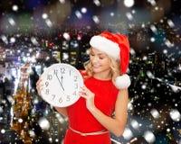 圣诞老人帮手帽子的微笑的妇女有时钟的 免版税库存照片