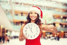 圣诞老人帮手帽子的微笑的妇女有时钟的 库存图片