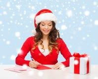 圣诞老人帮手帽子的微笑的妇女有明信片的 图库摄影