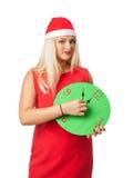 圣诞老人帮手帽子的微笑的妇女有显示12的时钟的 库存照片