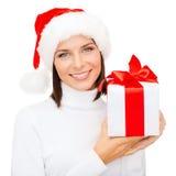 圣诞老人帮手帽子的微笑的妇女有礼物盒的 图库摄影
