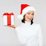 圣诞老人帮手帽子的微笑的妇女有礼物盒的 免版税库存照片