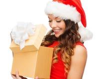 圣诞老人帮手帽子的微笑的妇女有礼物盒的 免版税图库摄影