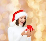 圣诞老人帮手帽子的微笑的妇女有礼物盒的 免版税库存图片