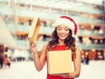 圣诞老人帮手帽子的微笑的妇女有礼物盒的 库存图片