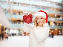 圣诞老人帮手帽子的微笑的妇女有红色心脏的 库存图片