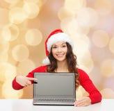 圣诞老人帮手帽子的微笑的妇女有膝上型计算机的 免版税库存图片