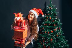 圣诞老人帮手帽子的微笑的妇女有许多礼物盒的 免版税库存图片