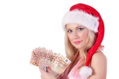 圣诞老人帮手帽子的微笑的妇女有金钱的 图库摄影