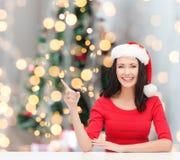 圣诞老人帮手帽子的微笑的妇女 免版税库存图片
