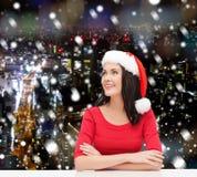 圣诞老人帮手帽子的微笑的妇女 免版税库存照片
