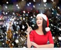 圣诞老人帮手帽子的微笑的妇女 图库摄影