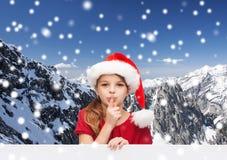 圣诞老人帮手帽子的微笑的小女孩 免版税库存图片