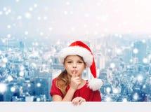 圣诞老人帮手帽子的微笑的小女孩 免版税库存照片