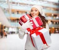 圣诞老人帮手帽子的微笑的少妇有礼物的 库存图片
