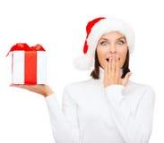 圣诞老人帮手帽子的惊奇的妇女有礼物盒的 免版税库存照片