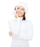圣诞老人帮手帽子的想法的和微笑的妇女 免版税库存图片