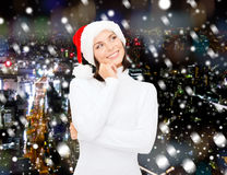 圣诞老人帮手帽子的想法的和微笑的妇女 免版税库存照片