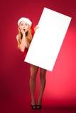 圣诞老人帮手帽子的愉快的妇女 免版税库存图片