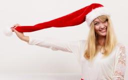 圣诞老人帮手帽子的愉快的逗人喜爱的妇女 圣诞节 图库摄影