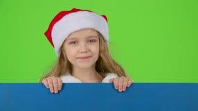 圣诞老人帮手看从一个蓝色委员会的后面并且闪光 绿色屏幕 股票视频
