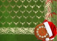 圣诞老人帽子、时钟和圣诞树与 免版税库存图片