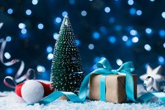 圣诞老人帽子、杉树和礼物盒有弓丝带的在雪背景 圣诞节或新年贺卡, bokeh作用 图库摄影