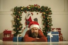 圣诞老人帽子举行当前箱子的圣诞节人在壁炉 图库摄影