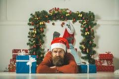 圣诞老人帽子举行当前箱子的圣诞节人在壁炉 免版税库存图片