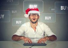 圣诞老人帽子买的材料的圣诞节人在网上 背景响铃拟订圣诞节赊帐节假日查出的红色购物闪耀的白色 免版税库存照片
