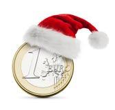 圣诞老人帽子和一枚欧洲硬币 免版税库存图片