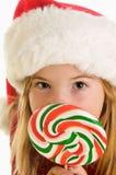 圣诞老人帽子和大圣诞节棒棒糖的一个逗人喜爱的小女孩 库存图片
