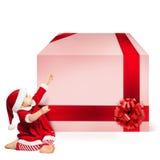 圣诞老人帽子和大礼物盒的圣诞节孩子 免版税图库摄影