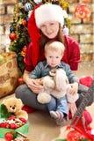 圣诞老人帽子和小男孩的少妇。 库存照片