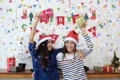 圣诞老人帽子和拿着的获得的礼物盒两个少妇乐趣 免版税库存图片