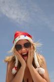 圣诞老人帽子和比基尼泳装的白肤金发的妇女 库存图片