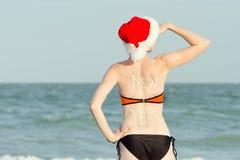 圣诞老人帽子和游泳衣的女孩调查距离 在后面的题字新年 在海岸视图之上 免版税库存图片