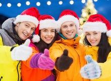 圣诞老人帽子和滑雪服的愉快的朋友户外 免版税库存图片