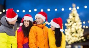 圣诞老人帽子和滑雪服的朋友在圣诞节 免版税库存图片