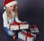 圣诞老人帽子和牛仔裤的举行美丽的小女孩微笑和 库存照片