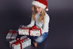 圣诞老人帽子和牛仔裤的美丽的小女孩微笑和拿着圣诞节礼物的 免版税库存照片