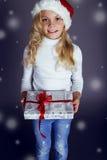 圣诞老人帽子和牛仔裤的美丽的小女孩微笑和拿着有圣诞节礼物的一个箱子 库存图片
