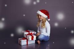 圣诞老人帽子和牛仔裤的美丽的小女孩微笑和拿着有圣诞节礼物的一个箱子 库存照片
