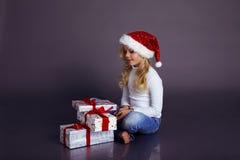 圣诞老人帽子和牛仔裤的美丽的小女孩微笑和拿着礼物的 图库摄影
