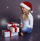 圣诞老人帽子和牛仔裤的美丽的小女孩微笑和拿着礼物的 库存图片