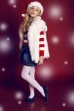 圣诞老人帽子和牛仔裤的美丽的小女孩微笑和拿着礼物的 免版税库存图片