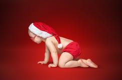 戴圣诞老人帽子和眼镜的小婴孩 库存图片