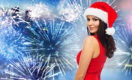 圣诞老人帽子和红色礼服的妇女在烟花 免版税库存图片