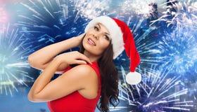 圣诞老人帽子和红色礼服的妇女在烟花 库存图片