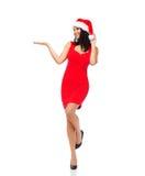 圣诞老人帽子和红色礼服的美丽的性感的妇女 免版税库存图片